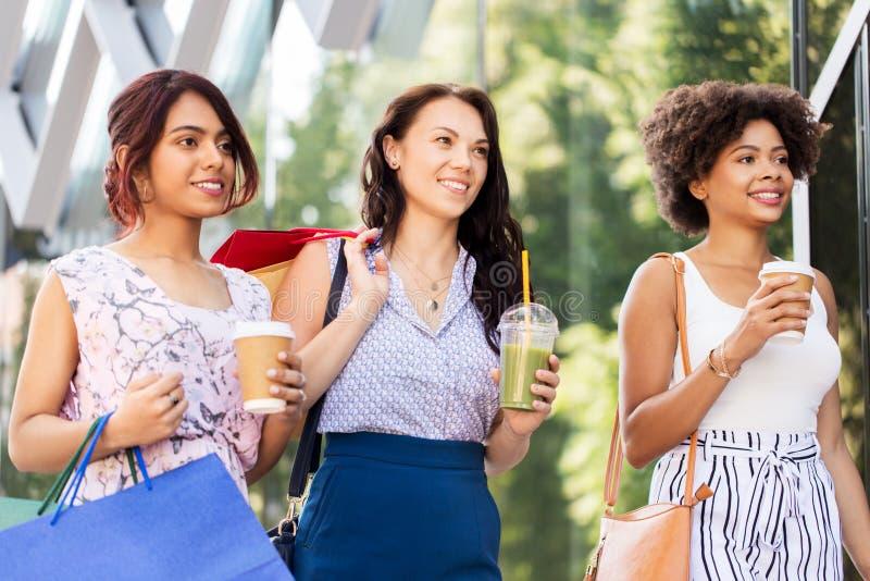 Kvinnor med shoppingp?sar och drinkar i stad royaltyfria bilder
