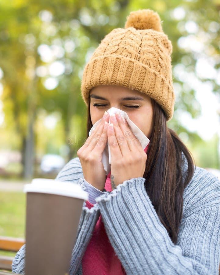 Kvinnor med silkespappret som har influensa eller allergi i höst royaltyfri fotografi