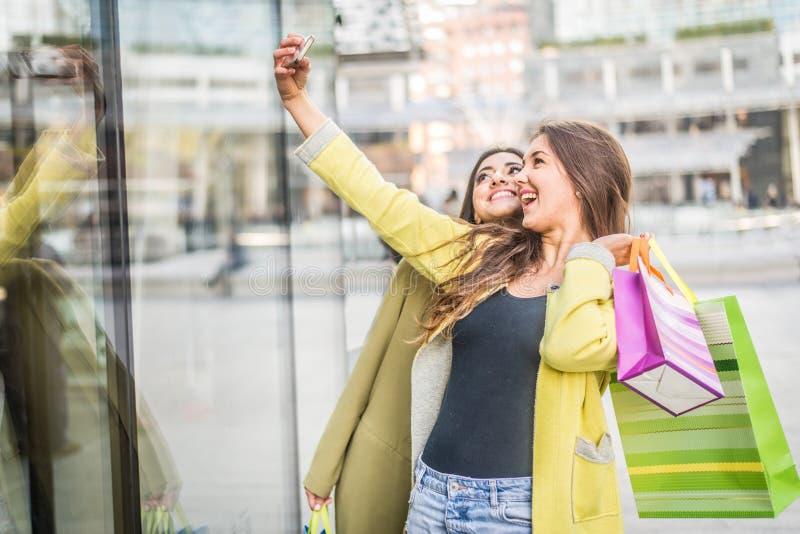 Kvinnor med smartphones i en stång arkivfoto