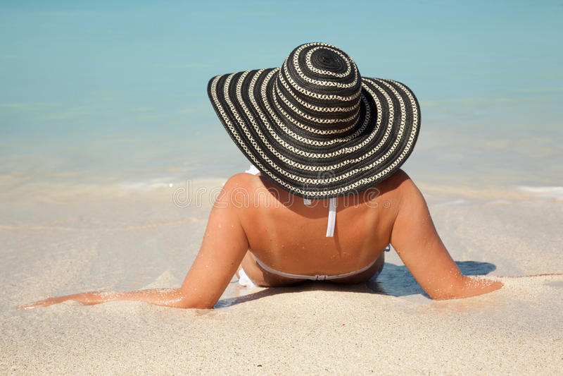 Kvinnor med solhatten i havet royaltyfria bilder