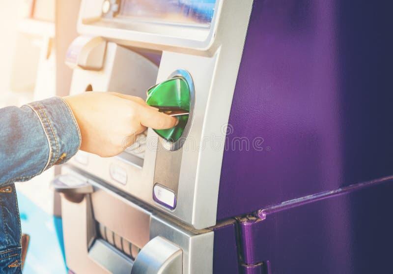 Kvinnor nand som sätter in ATM-kreditkorten in i bankmaskinen royaltyfria foton