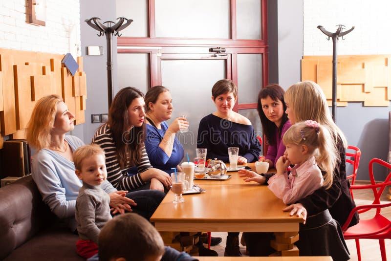 Kvinnor och barn som har en drink arkivbilder