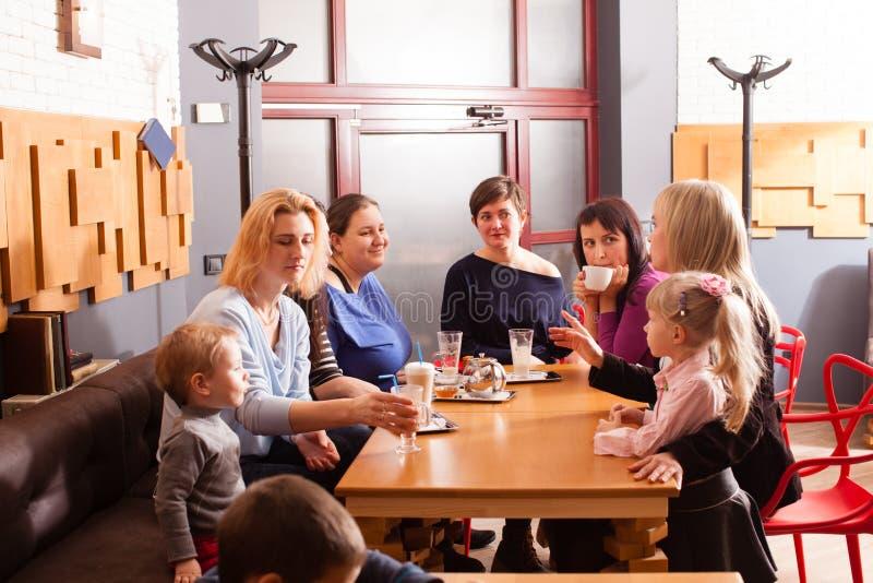 Kvinnor och barn som har en drink fotografering för bildbyråer