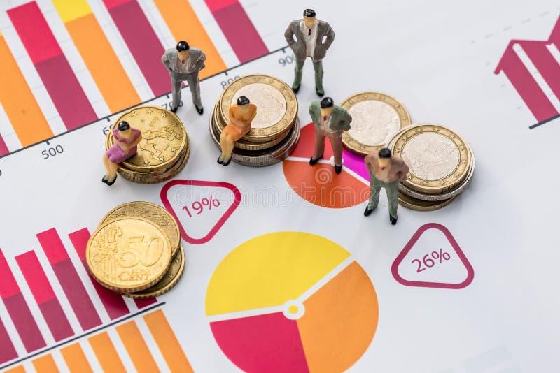 Kvinnor och män på affärsgraf och på mynt arkivbild