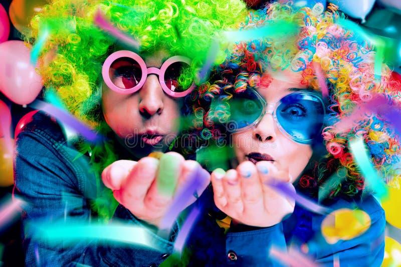 Kvinnor och män som firar på partiet för helgdagsafton eller karneval för nya år arkivfoton