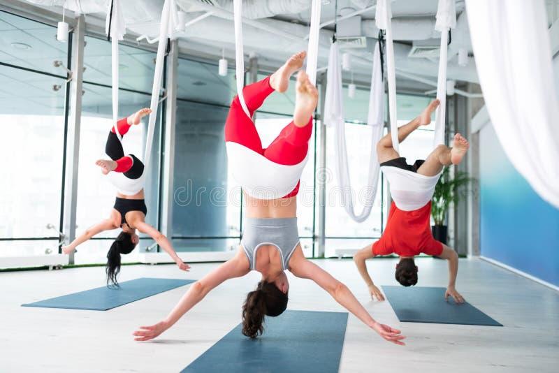 Kvinnor och mankänsla som förbluffar, medan öva flyg- yoga royaltyfria bilder