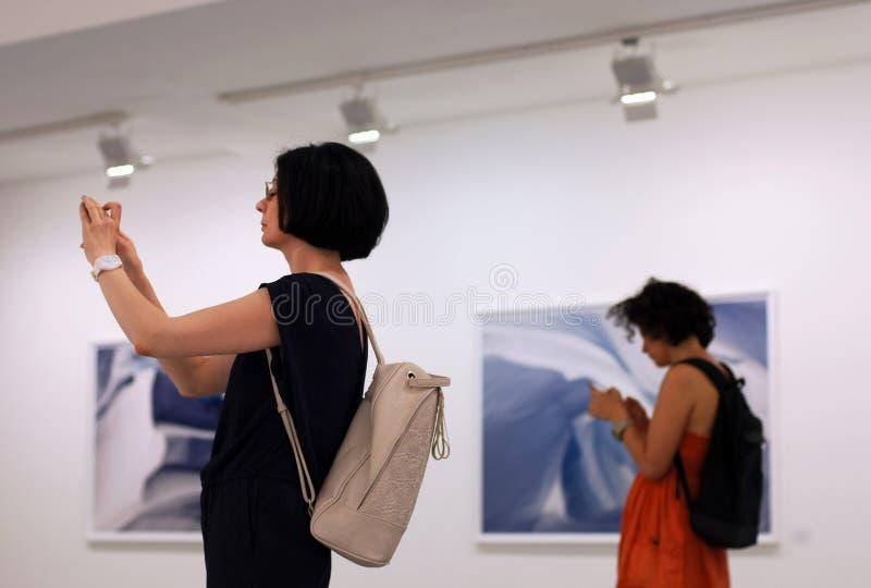 Kvinnor på fotoexhitionen genom att använda smartphones, mobila enheter och social nätverksböjelse royaltyfri foto