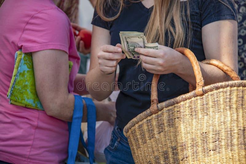Kvinnor på marknaden med påsar och en oigenkännlig sugrörkorg - flicka i fron som ut räknar US dollar - royaltyfri fotografi