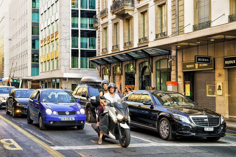 Kvinnor på motorcykeln och bilar i gata i Genève royaltyfri foto