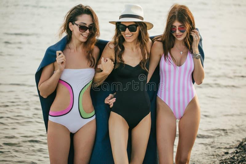 Kvinnor på stranden med plädet efter aftonen, sommarsemester, ferier, lopp arkivfoton