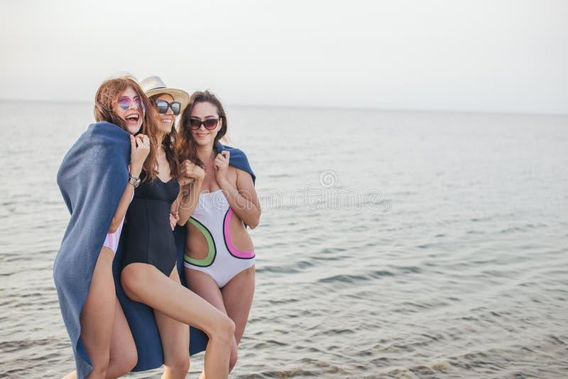 Kvinnor på stranden med plädet efter aftonen, sommarsemester, ferier, lopp arkivbild