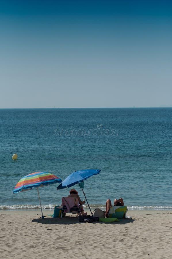 kvinnor på stranden som sitter på stol med paraplyet på tillbaka sikt fotografering för bildbyråer