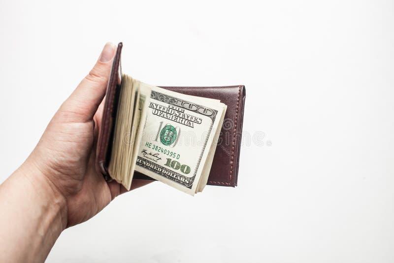 Kvinnor räcker att rymma en plånbok mycket av hundra dollarräkningar som isoleras över en vit bakgrund royaltyfria bilder