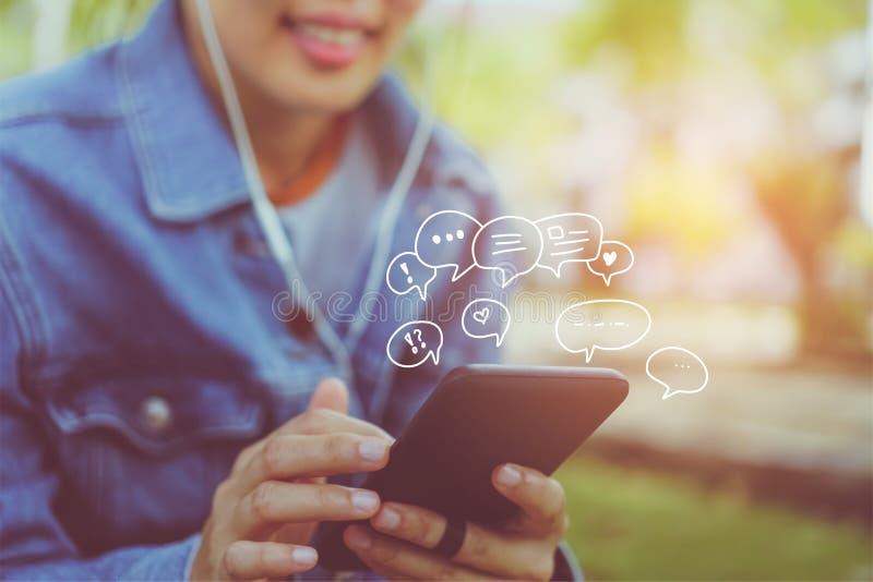 Kvinnor räcker genom att använda smartphonemaskinskrivning som pratar royaltyfri foto