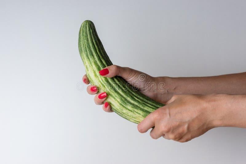 Kvinnor räcker innehavgurkan som en mans penis på vit bakgrund Erotiskt begrepp arkivbilder