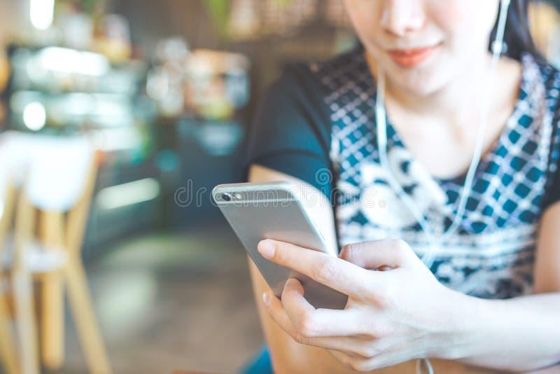 Kvinnor räcker lyssnar till musik från mobiltelefoner royaltyfri bild