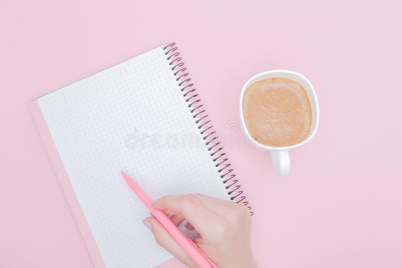 Kvinnor räcker med handstil på mellanrum för anmärkningsbok på den rosa bakgrunden, instagramen och affärsidéen arkivbilder