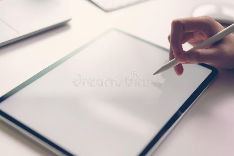 Kvinnor r?cker anv?nder minnestavlan p? skrivbordet Ta din sk?rm till den p?lagda advertizingen arkivfoto