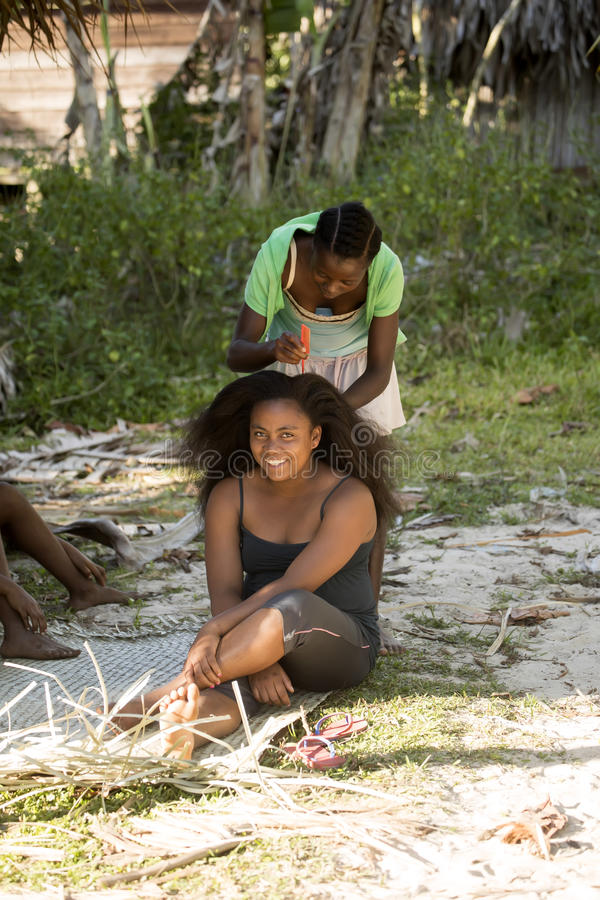Kvinnor reglerar ömsesidigt hår, Madagascar royaltyfri bild