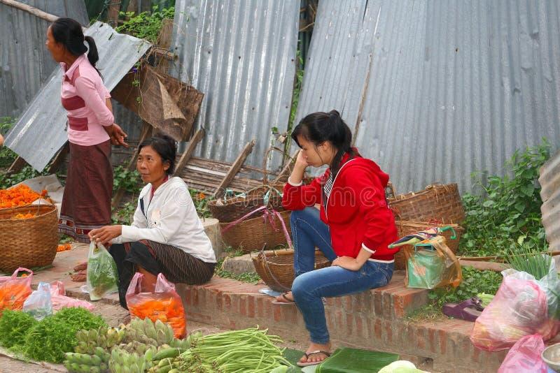Kvinnor säljer nya frukter, och grönsaker på morgonen marknadsför i Luang Prabang i Laos arkivfoto