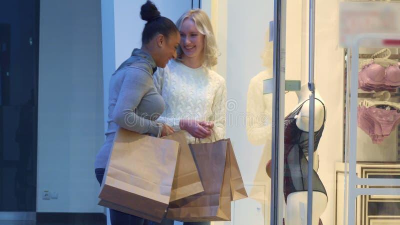 Kvinnor ser underkläderna till och med lagerfönstret arkivfoton