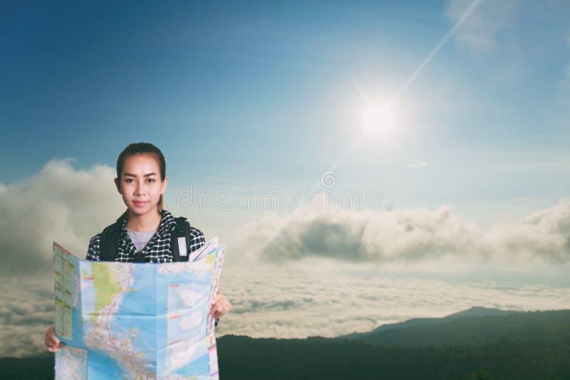 Kvinnor som är asiatiska med ryggsäcken som tycker om solnedgång på maximum av berget, l royaltyfria foton