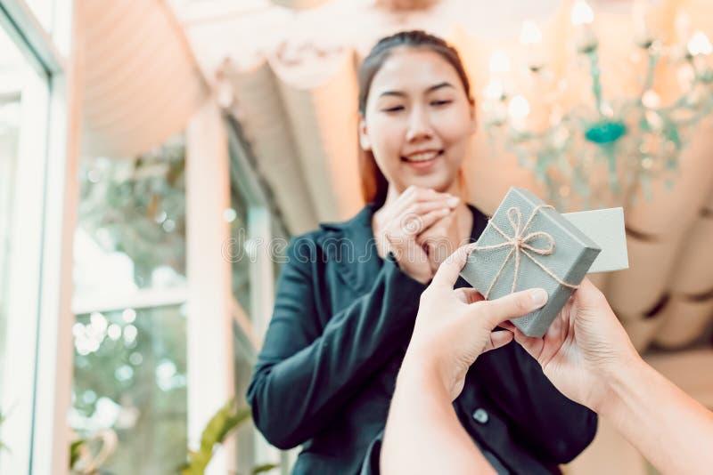 Kvinnor som är lyckliga med gåvaasken från en man arkivbild