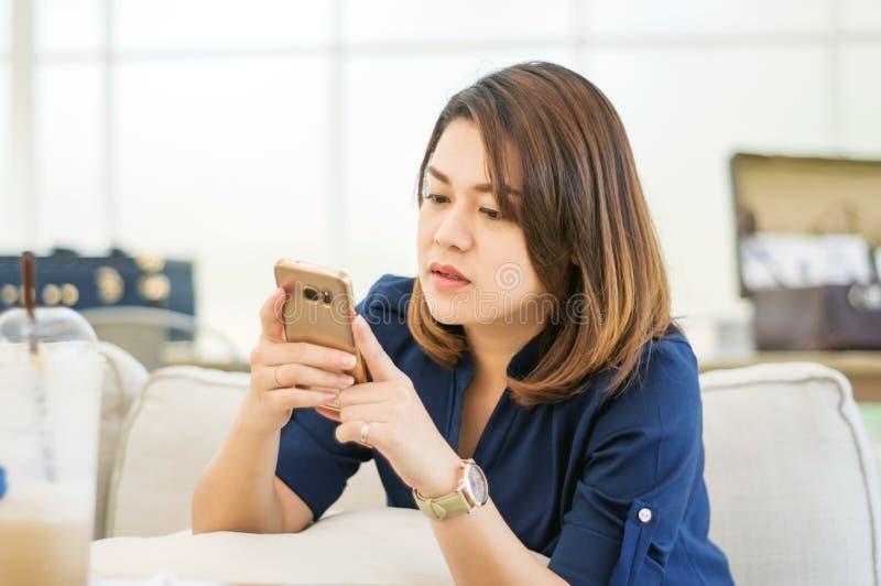 Kvinnor som använder en smartphone arkivfoton