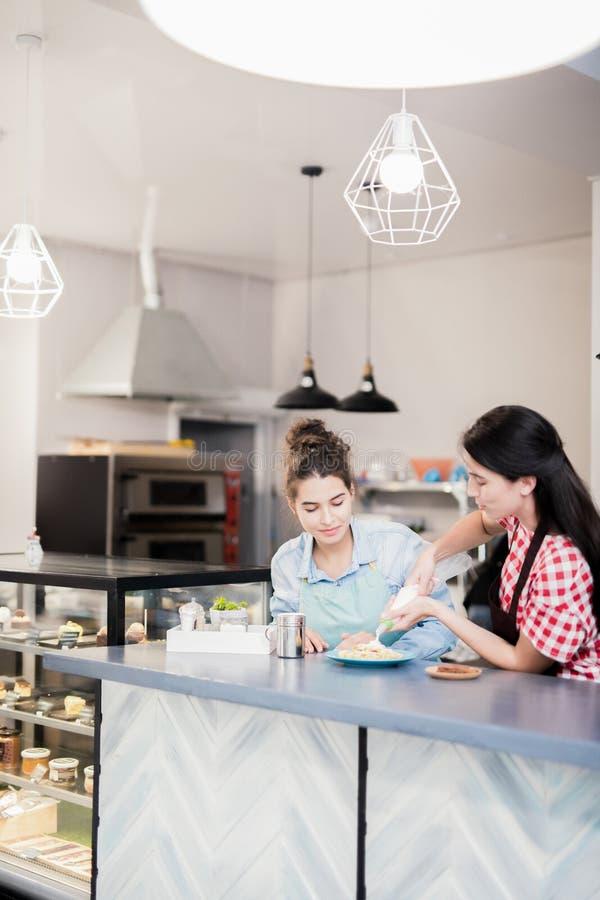 Kvinnor som arbetar i kaka, shoppar fotografering för bildbyråer
