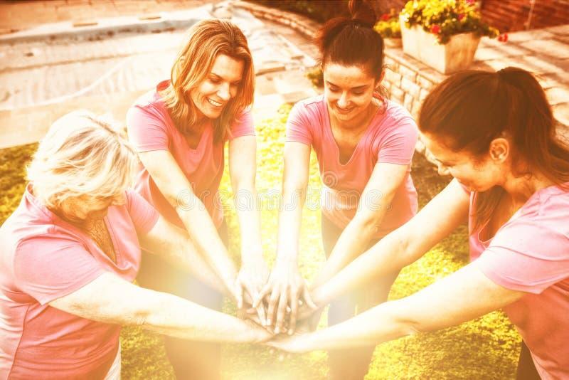 Kvinnor som bär den rosa skjortan som tillsammans sätter händer royaltyfria foton