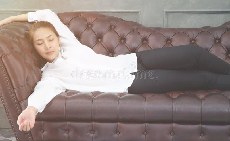 Kvinnor som bär en vit skjorta som hon sover på soffan royaltyfria foton