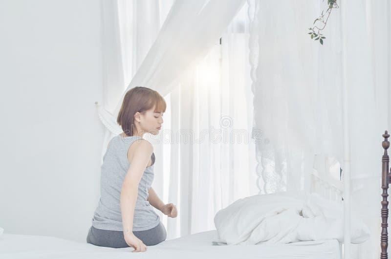 Kvinnor som bär grå pyjamas som sitter på soffan, använder handtaget till foten arkivfoton