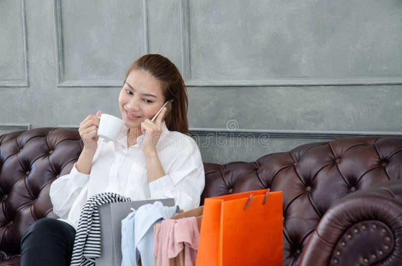 Kvinnor som bär lyckliga orange shoppa påsar arkivbilder