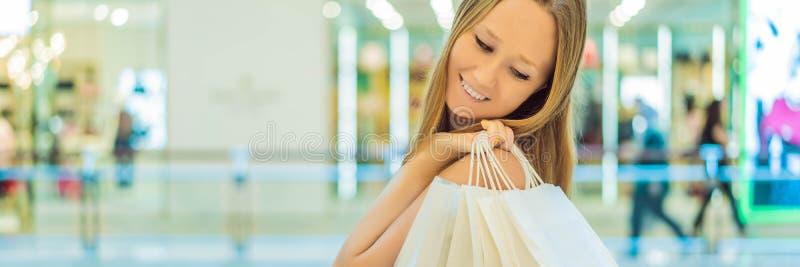 Kvinnor som bär många shoppa påsar i det suddiga shoppinggalleriaBANRET, LÅNGT FORMAT arkivbild