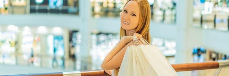 Kvinnor som bär många shoppa påsar i det suddiga shoppinggalleriaBANRET, LÅNGT FORMAT royaltyfri fotografi