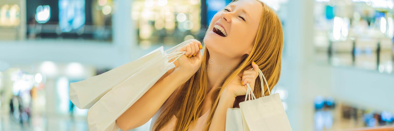 Kvinnor som bär många shoppa påsar i det suddiga shoppinggalleriaBANRET, LÅNGT FORMAT arkivfoto