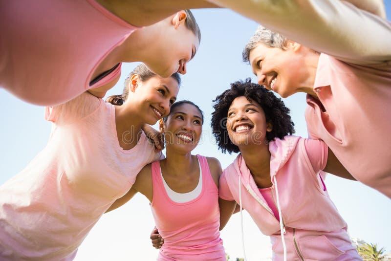 Kvinnor som bär rosa färger för bröstcancer med armar omkring fotografering för bildbyråer