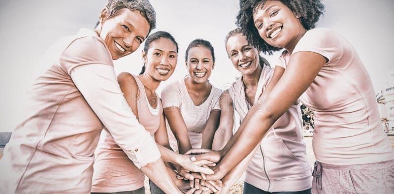 Kvinnor som bär rosa färger för bröstcancer och tillsammans sätter händer arkivbilder
