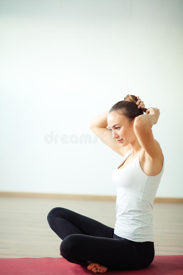 Kvinnor som förbereder sig för att göra yoga gör frisyren royaltyfri foto