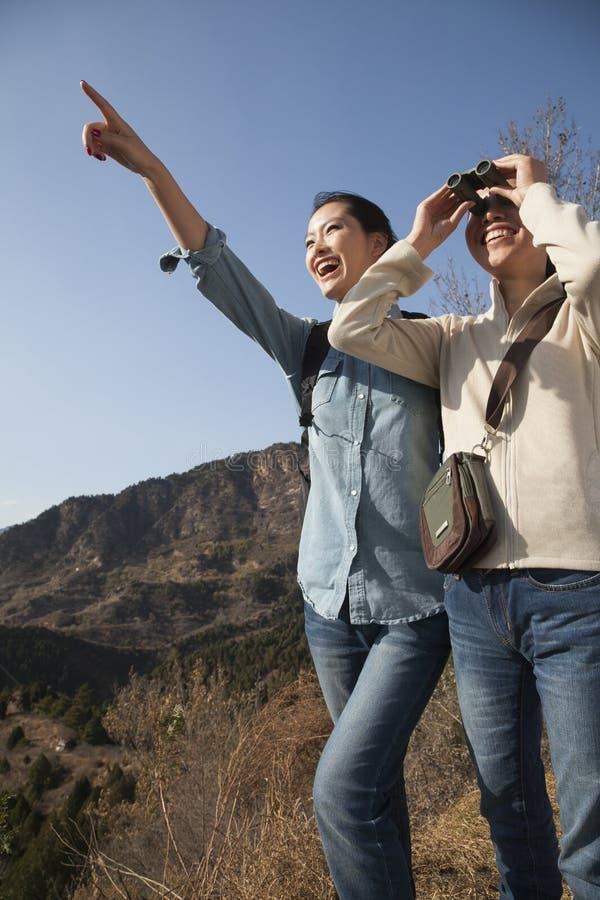 Kvinnor som fotvandrar, genom att använda kikare som pekar på bergöverkanten arkivfoton