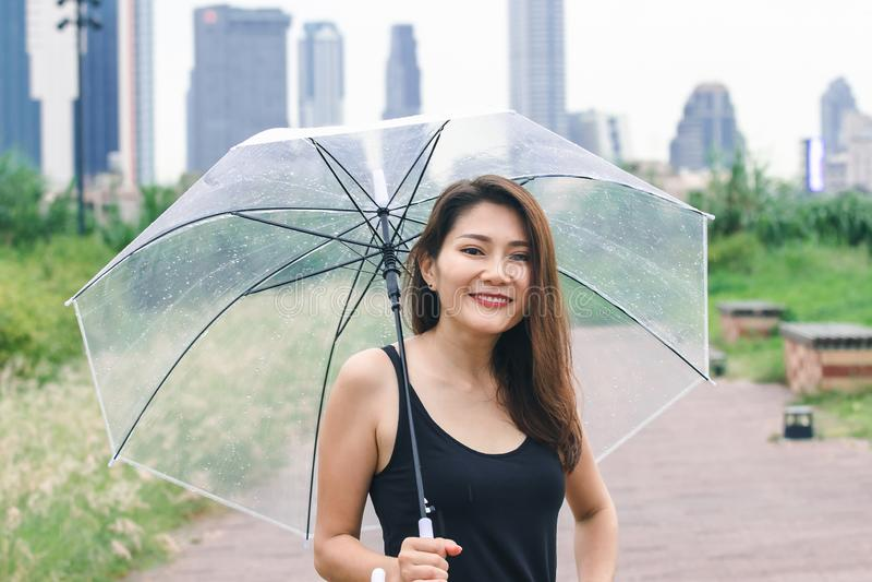 Kvinnor som går paraplyet i, parkerar royaltyfri bild