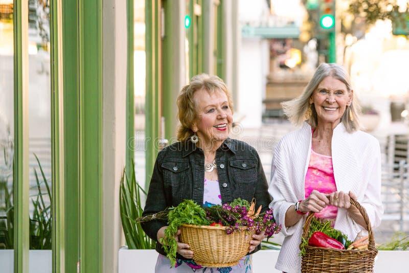 Kvinnor som går tillbaka med korgar av grönsaker från bönder, marknadsför arkivbilder