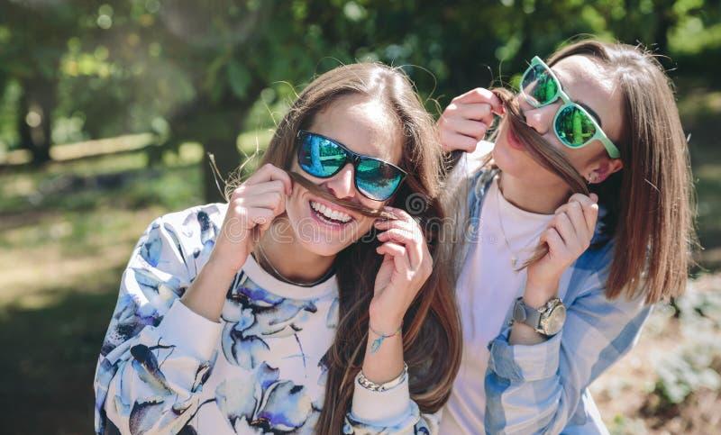 Kvinnor som gör mustascher med hår och att skratta arkivbilder