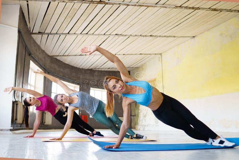 Kvinnor som gör statisk övning under gruppgenomkörare royaltyfria foton