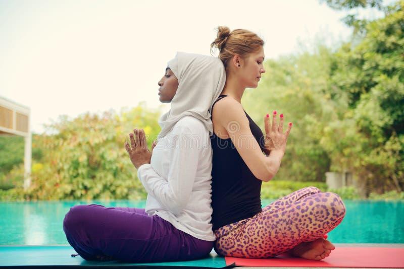 Kvinnor som gör yoga vid poolsiden royaltyfri foto