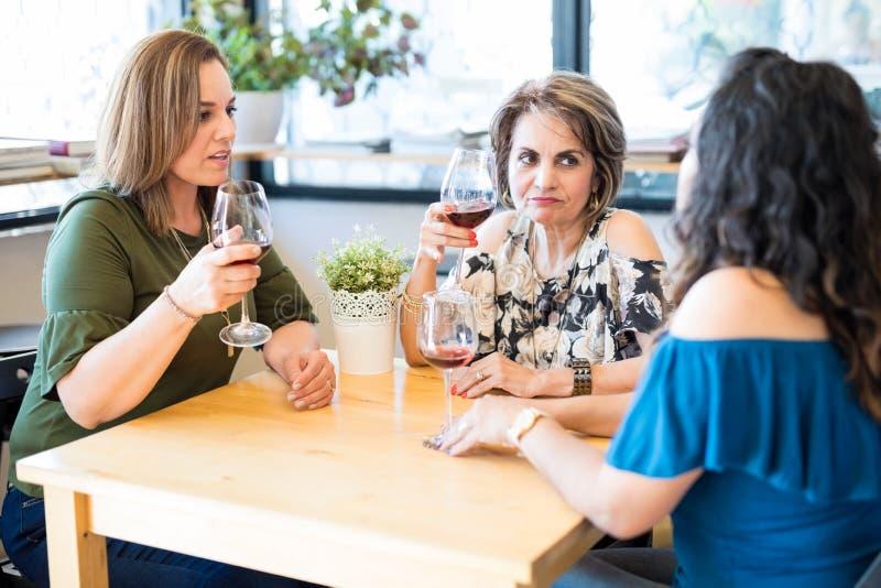 Kvinnor som har allvarlig diskussion på restaurangen royaltyfri foto