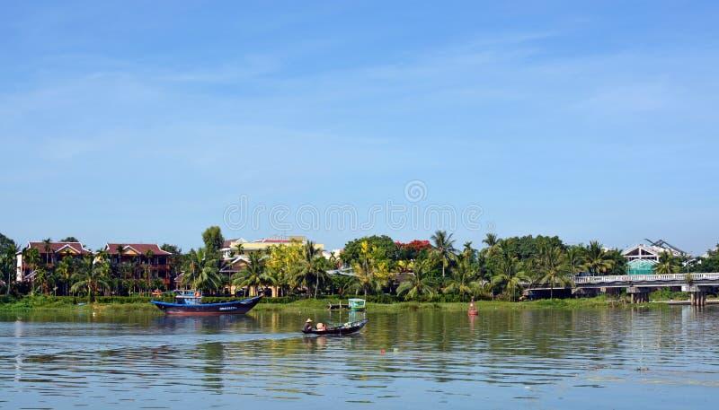 Kvinnor som hem går tillbaka över Hoi An River från marknad royaltyfri fotografi