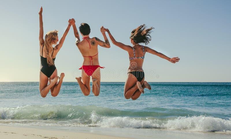Kvinnor som hoppar i luft och tycker om på stranden arkivfoton