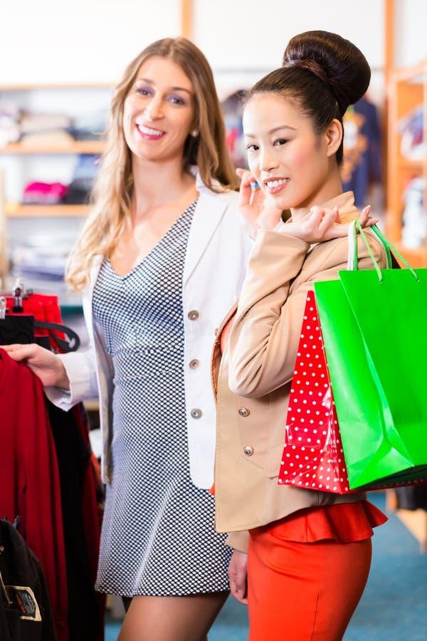Kvinnor som köper mode shoppar eller lagrar in royaltyfri foto