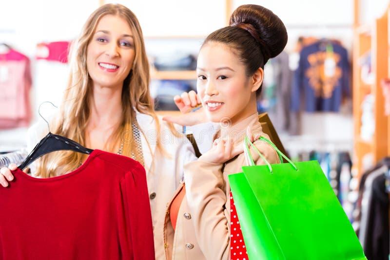 Kvinnor som köper modekläder shoppar eller lagrar in royaltyfri foto
